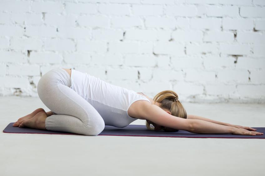 Pregnant young woman doing prenatal Child Yoga Pose, Balasana
